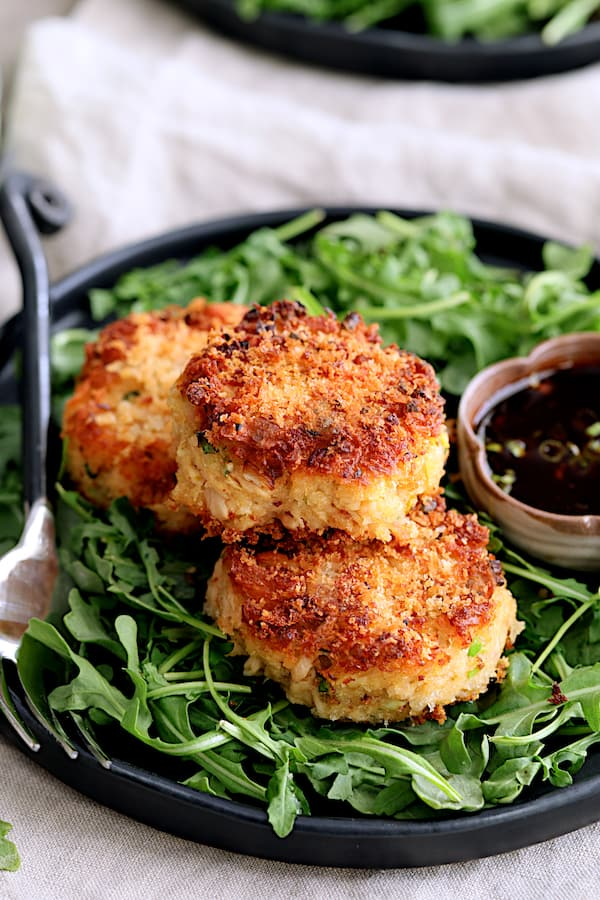 Photo of Tuna Kimchi Cakes with Soy Ginger Dipping Sauce on black plate with arugula and dipping sauce.