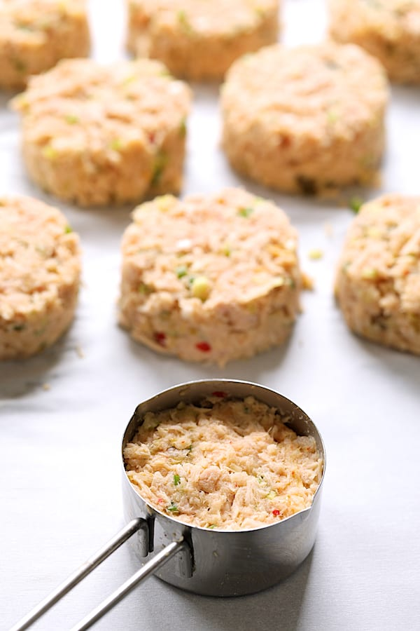 Photo of tuna cake mixture in measuring cup with formed cakes in the background.