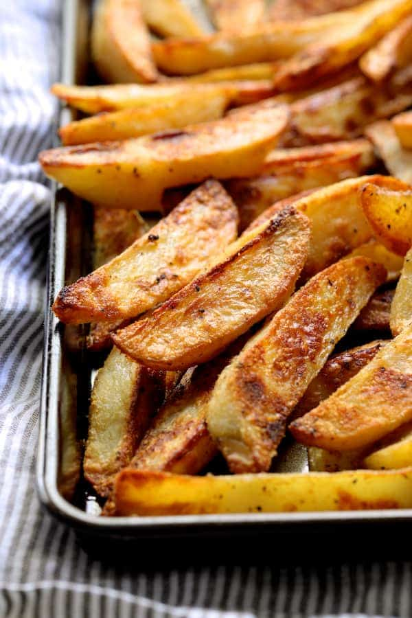 Close-up photo of cooked oven fries on baking sheet.
