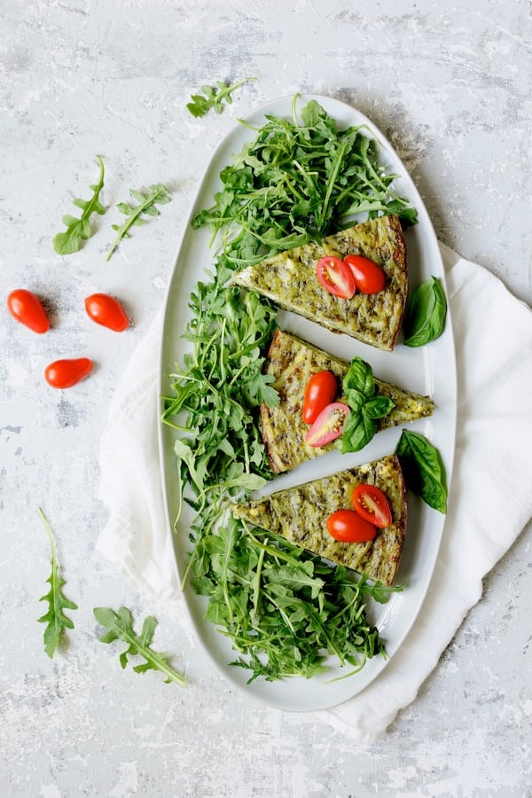 Photo of Easy Hash Brown Frittata with Pesto and Goat Cheese on white oval platter garnished with grape tomatoes and arugula.