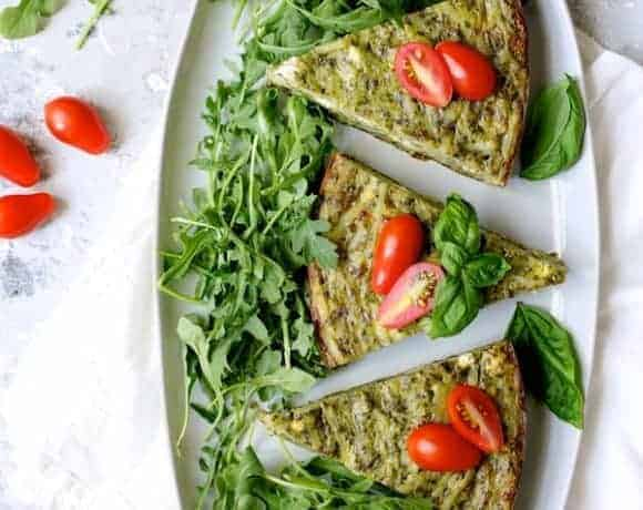 Easy Hash Brown Frittata with Pesto and Goat Cheese - On white platter, cut into wedges, garnished with arugula and tomatoes