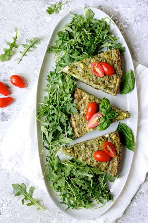 Photo of Easy Hash Brown Frittata with Pesto and Goat Cheese on white platter, cut into wedges, garnished with arugula and grape tomatoes.