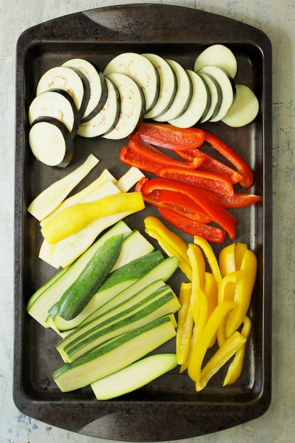 Photo of uncooked vegetables on baking sheet sliced and ready for the grill.