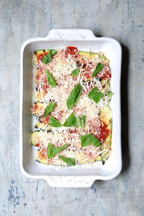 Photo of first layer in white baking dish of zucchini, some marinara and fresh basil.