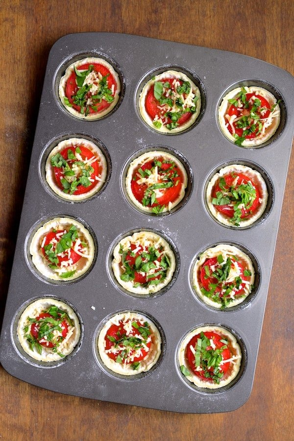 Mini Southern Tomato Pies - Assembly process with first layer to tomatoes topped with more cheese and basil