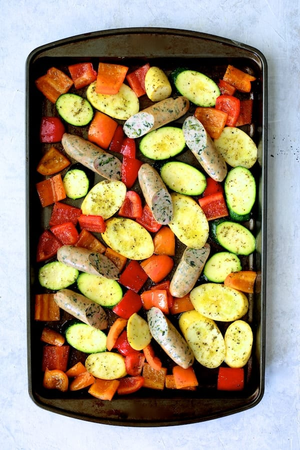 Photo of cut vegetables on baking sheet with sausage added.