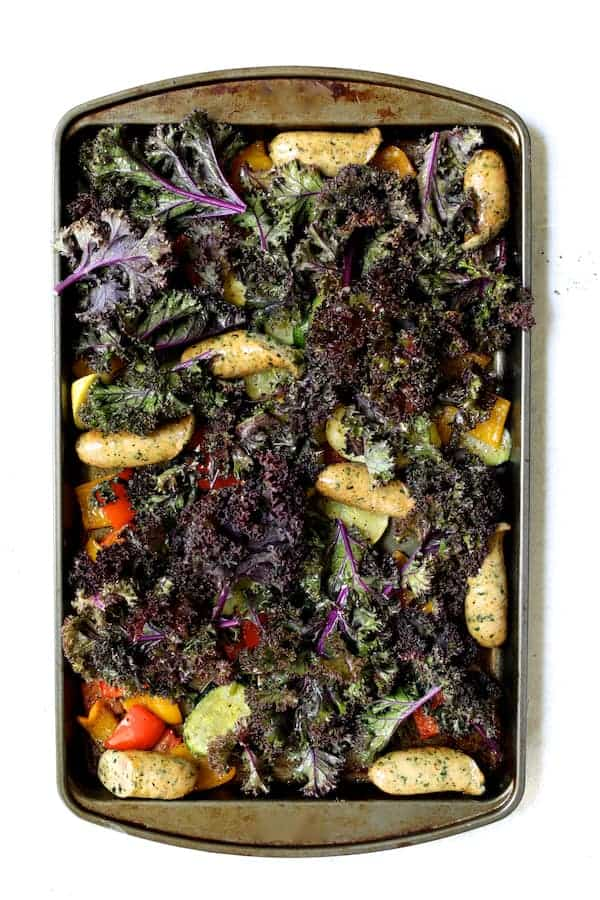 Photo of vegetables and sausage on baking sheet with kale added.