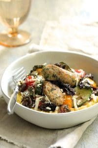 Sheet Pan Mediterranean Chicken Sausage and Vegetables with Garlic Parmesan Polenta - Finished product ready to eat sprinkled with cheese on beige napkin