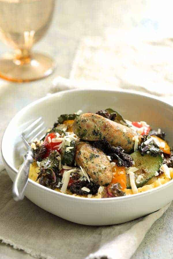Photo of Mediterranean Sheet Pan Chicken Sausage and Vegetables with Garlic Parmesan Polenta in white bowl with fork ready to eat.
