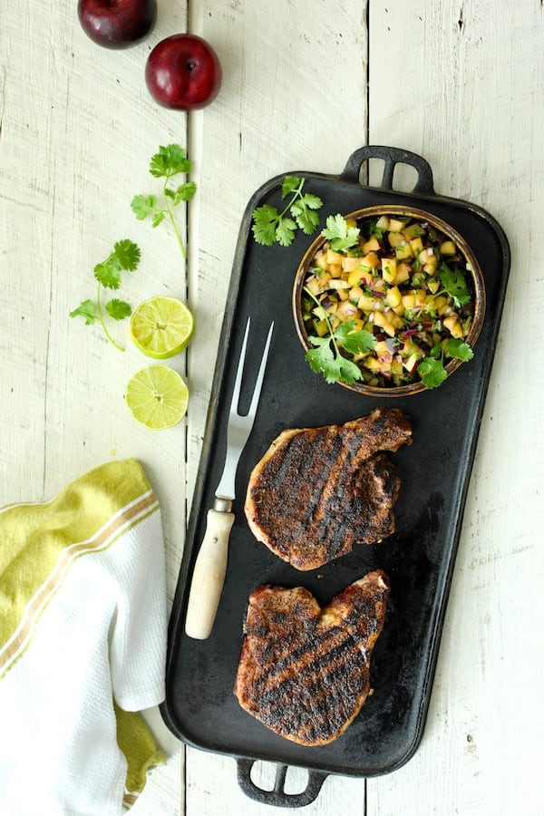 Southwestern Spice Grilled Pork Chops with Plum Jalapeño Salsa - Overhead shot of pork chops with salsa and white wood background