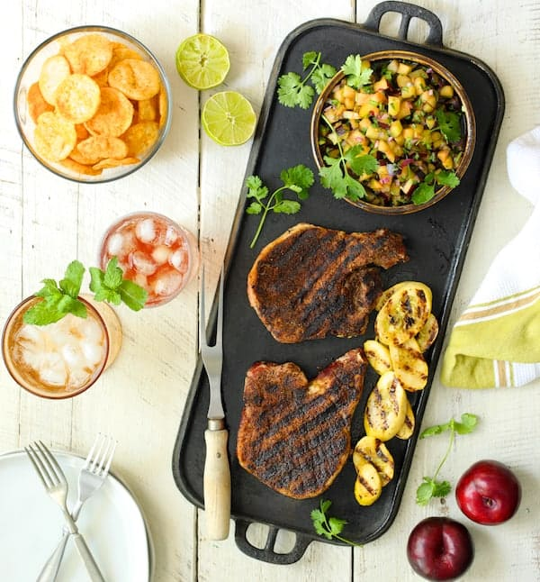 Southwestern Spice Grilled Pork Chops with Plum Jalapeño Salsa with chips, tea and grilled vegetables on white wood background