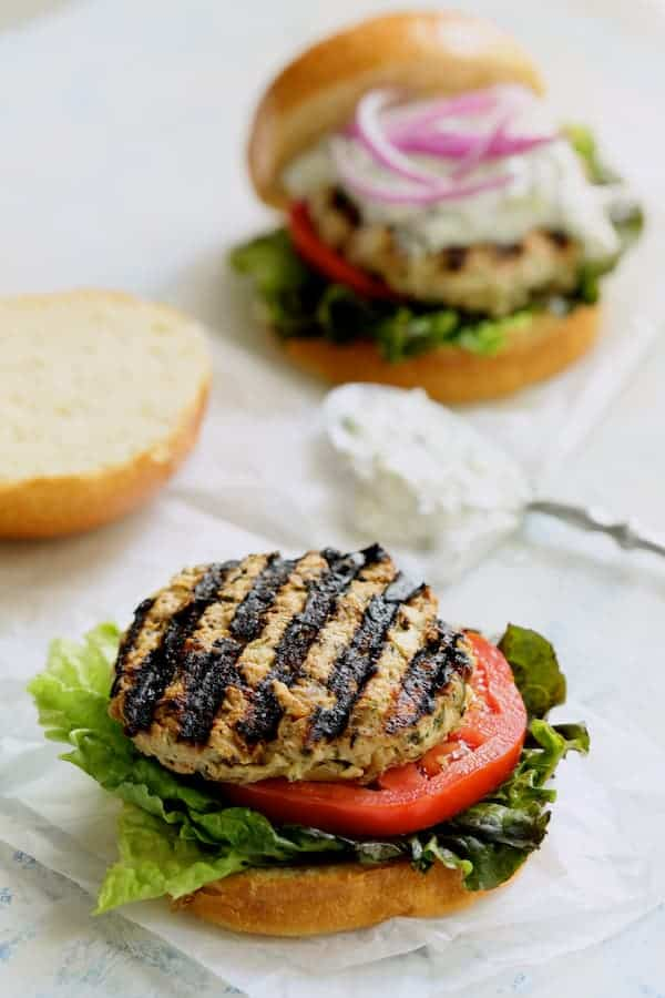 Chicken Zucchini Feta Burgers with Jalapeño Tzatzik - Another photo of the bare burger with tzatziki sauce in the background