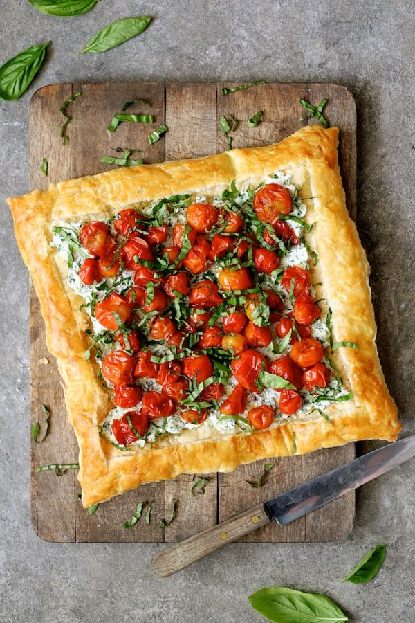 Roasted Cherry Tomato Tart with Herbed Ricotta - Overhead shot of tart on wood cutting board before being sliced