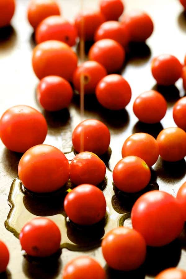 Roasted Cherry Tomato Tart with Herbed Ricotta - Tomatoes on baking sheet being drizzled with olive oil