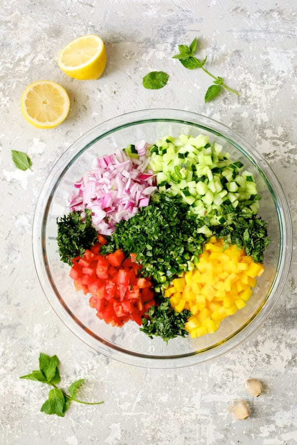 Photo of salad ingredients in glass mixing bowl before being stirred.