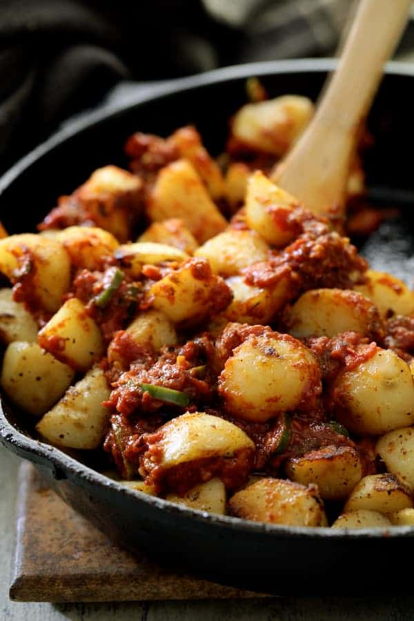 Patatas Bravas Chilenos - Close-up shot of potatoes being stirred with sauce in cast iron skillet