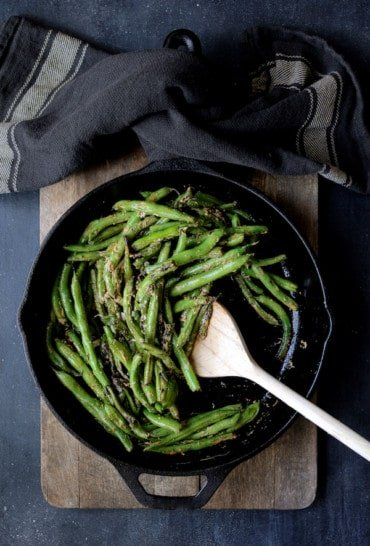 Skillet Charred Green Beans with Goat Cheese Chipotle Butter - Hero shot of beans in cast iron skillet being stirred with wooden spoon