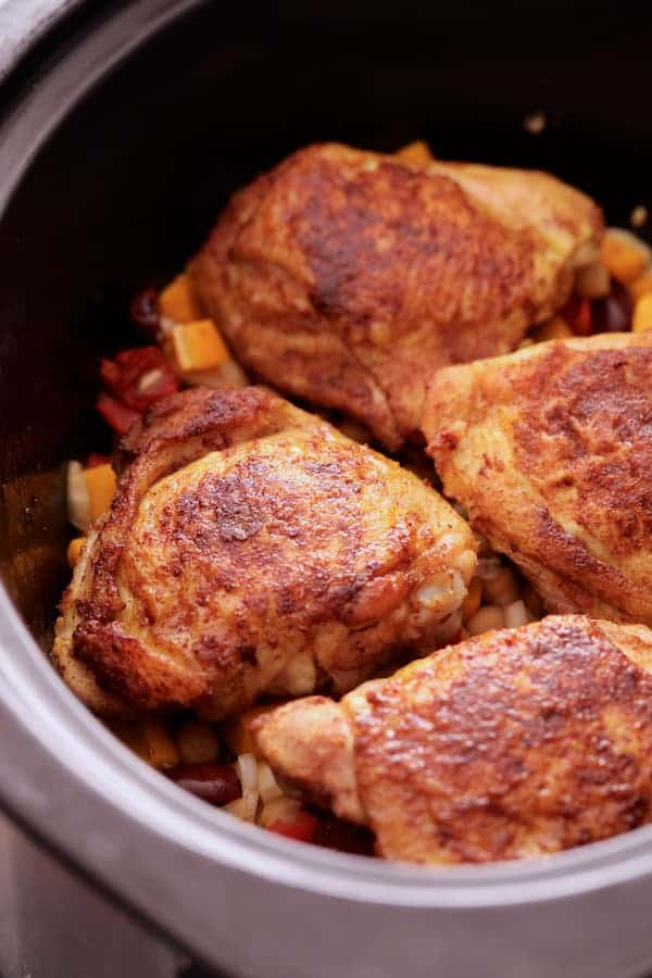 Photo of chicken thighs in slow-cooker after being browned.