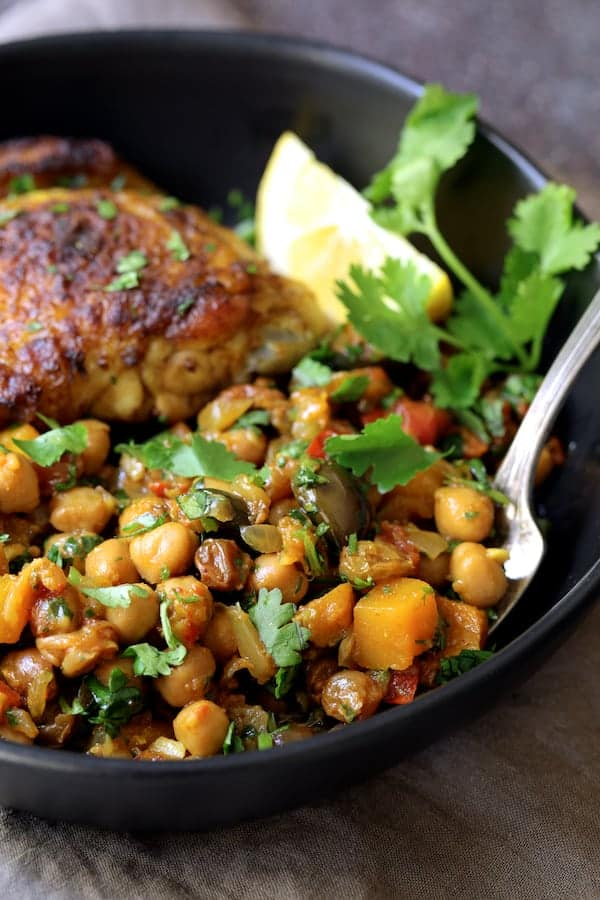 Moroccan Chicken Tagine with Butternut Squash Chickpeas and Olives - Close-up shot of butternut squash, chickpea and olive combination in black bowl