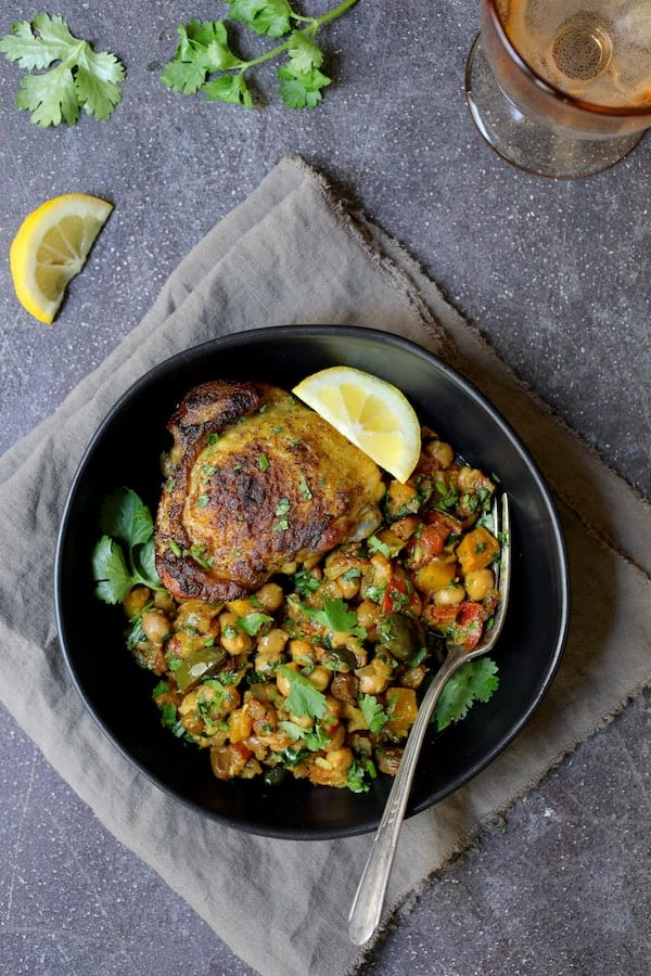 Photo of one serving of Moroccan Chicken Tagine with Butternut Squash, Chickpeas and Olives in black bowl.