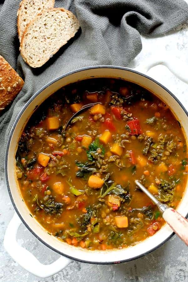 Spicy Kale Butternut Squash and Lentil Soup with Bacon - Overhead closeup shot of soup in white Dutch oven