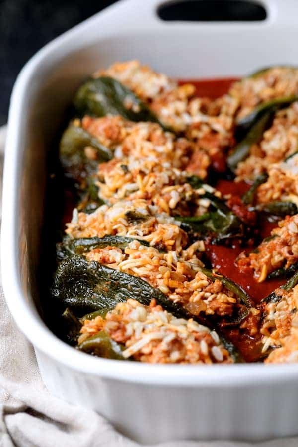Chorizo and Brown Rice Stuffed Poblano Peppers - Stuffed peppers in white baking dish before being sauced and baked