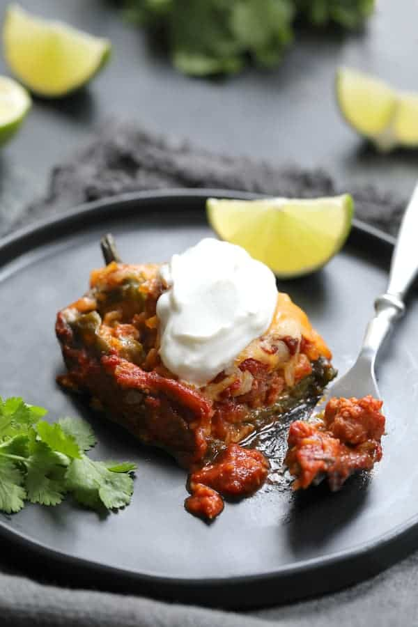 Chorizo and Brown Rice Stuffed Poblano Peppers - Single pepper on plate garnished with lime wedge, cilantro and dollop of sour cream