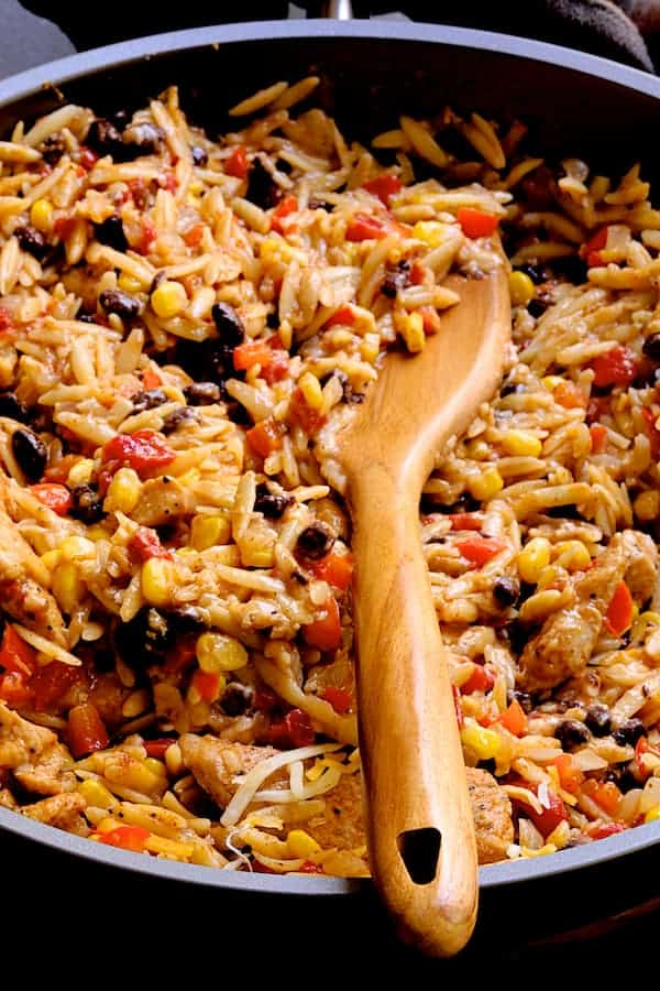 Close-up photo of Southwestern Chicken Orzo and Black Bean Skillet with wooden spoon.