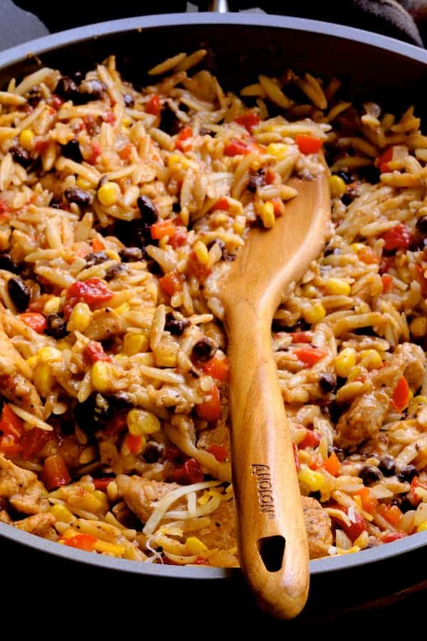 Southwestern Chicken Orzo and Black Bean Skillet - Finished dish being stirred with wooden Anolon spoon