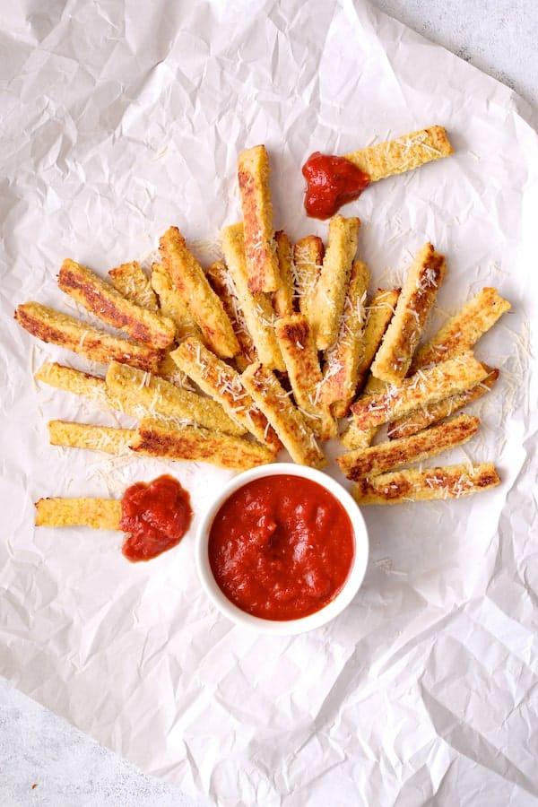 Spaghetti Squash Fries on white paper with marinara sauce