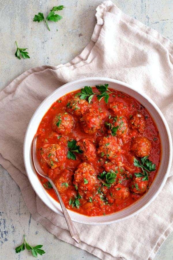 Spiced Meatballs with Tomato Sauce - Overhead hero shot of meatballs in tomato sauce in white bowl