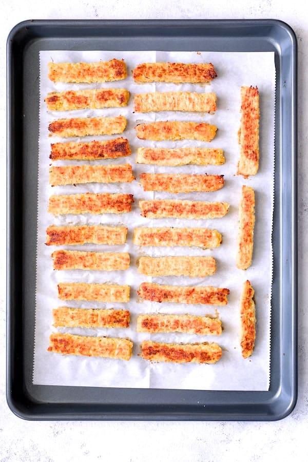 Spaghetti Squash Fries - Baked spaghetti squash fries on parchment paper on baking sheet