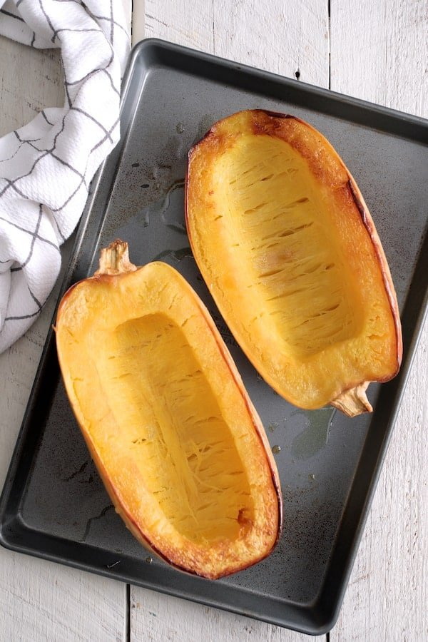 Spaghetti Squash Fries - Cooked halved spaghetti squash on baking sheet with white and blue towel