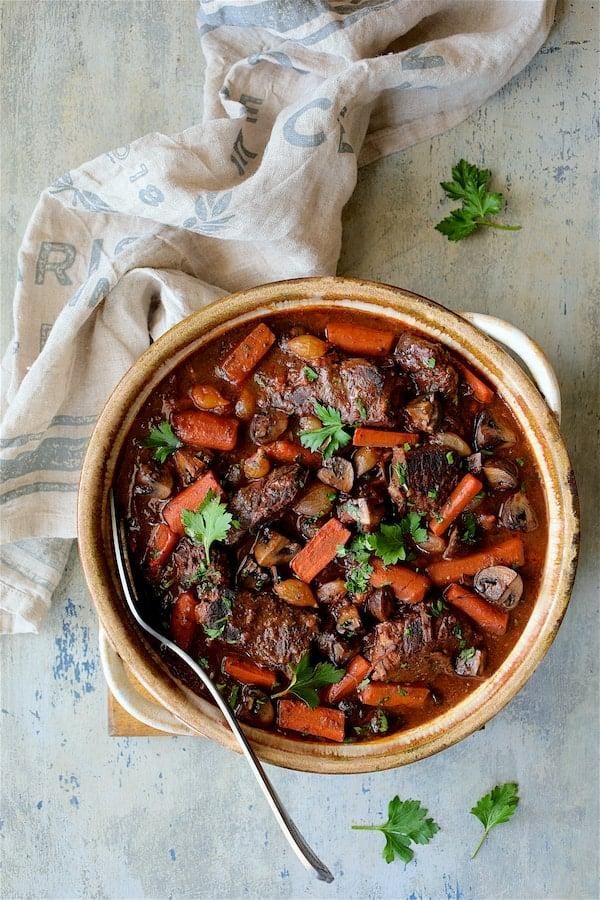 Boneless Beef Short Ribs Bourguignon - Overhead hero shot of beef in clay serving dish