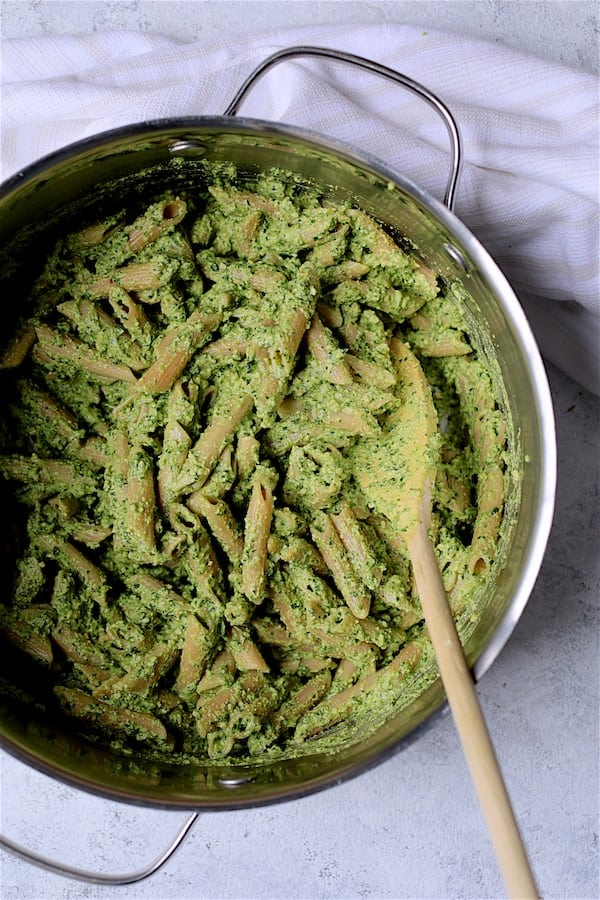 Modern Table Pasta with Creamy Cashew and Spinach Pesto Sauce - Overhead shot of pesto and pasta being combined in cooking pot