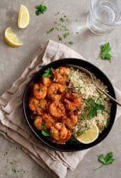 The Best Shrimp Creole - Overhead shot in black bowl with rice, garnished with lemon wedges and parsley
