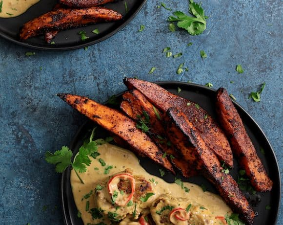 Spicy Tahini Pork Medallions with Harissa Roasted Sweet Potato Wedges - Overhead hero close-up shot on blue background