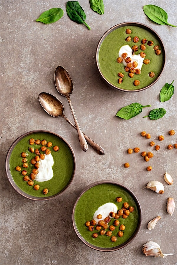 Spinach and Goat Cheese Bisque with Crispy Lemon Chickpeas - Overhead shot farthest away with three bowls of soup garnished with yogurt, chickpeas with spinach and garlic scattered around