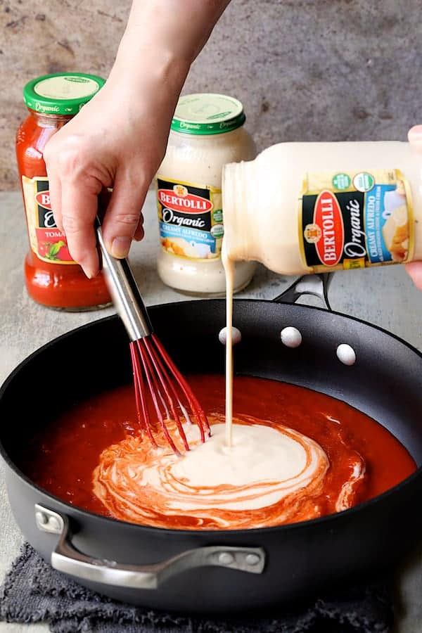 Photo of marinara and Alfredo sauces being combined in skillet with whisk.