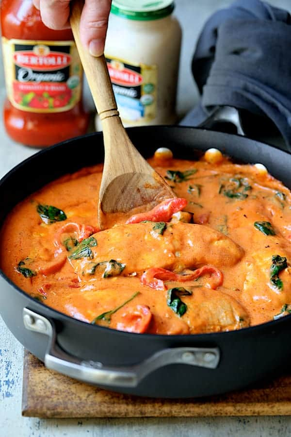 Photo of Chicken in Rosa Sauce with Roasted Red Bell Pepper and Spinach in skillet being stirred with wooden spoon.