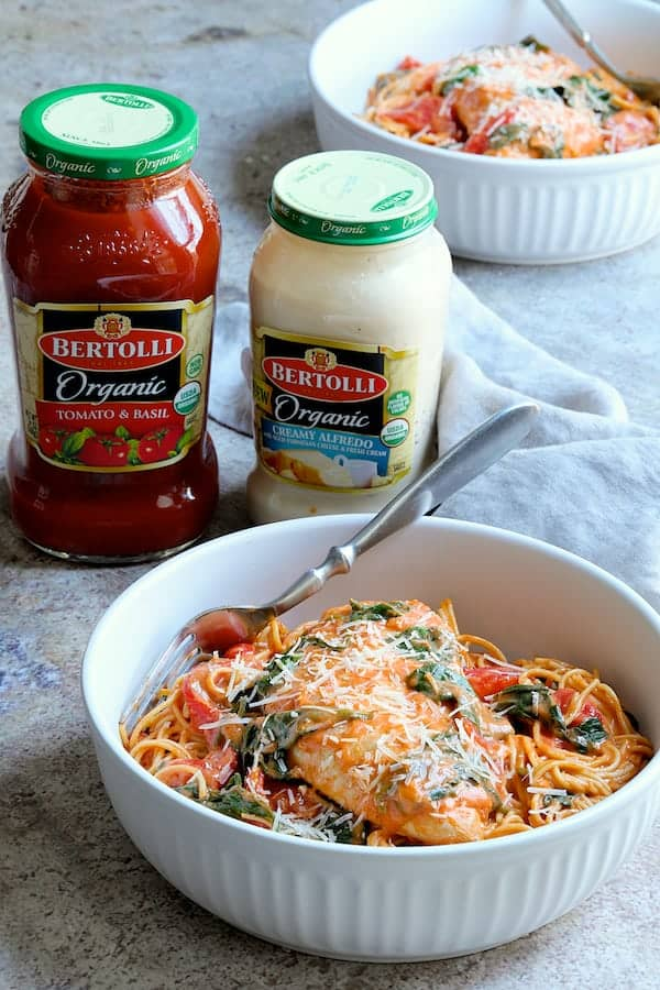 Photo of a serving of Chicken in Rosa Sauce with Roasted Red Bell Pepper and Spinach with jars of the sauces used in the background.