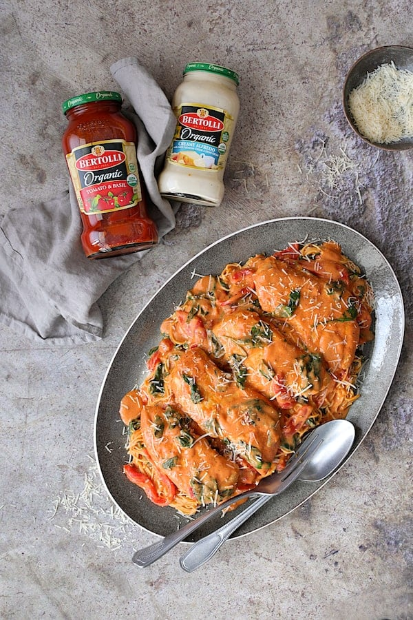 Photo of Chicken in Rosa Sauce with Roasted Red Bell Pepper and Spinach over angel hair pasta on gray-rimmed platter with Bertolli jars nearby.