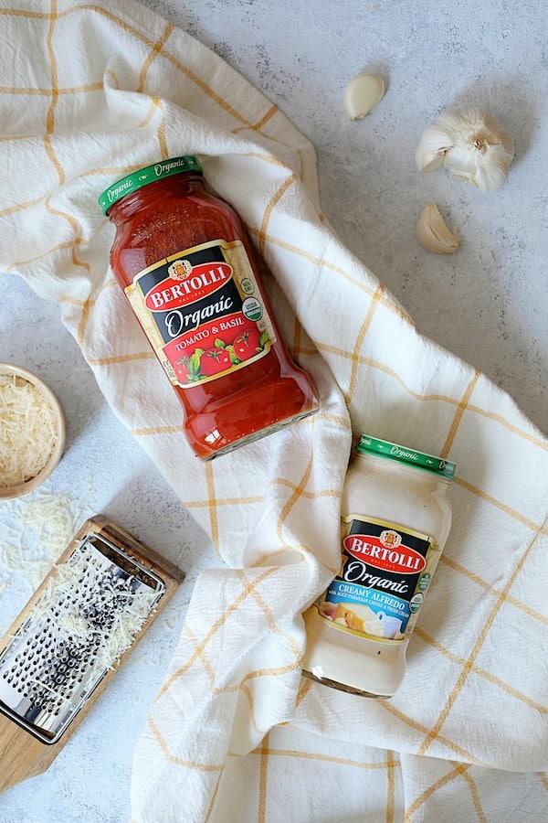 Photo of Bertolli marinara sauce and Alfredo sauce on yellow checked towel.