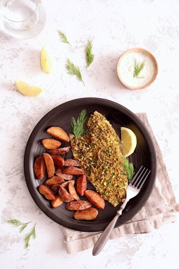 Photo of Pistachio-Crusted Fish with Lemon-Dill Aioli served with roasted potatoes garnished with lemon slices and dill sprigs on black plate.