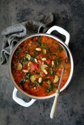 Smoky Spanish Vegetable and White Bean Soup with Kale - Another overhead shot slightly farther away with soup in white Dutch oven on gray background with gray napkin and ladle