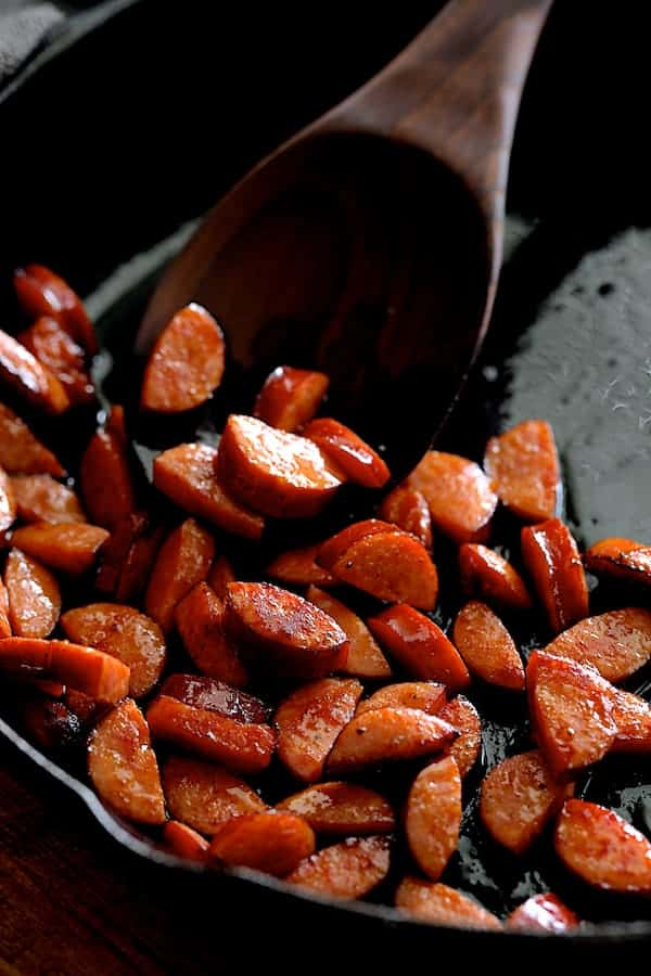 Photo of Andouille sausage being sauteed in cast iron skillet being stirred with wooden spoon