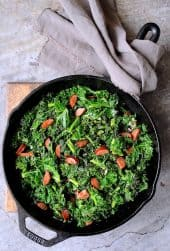 Spicy Sautéed Kale with Andouille Sausage - Overhead shot of dish in cast iron skillet on wooden trivet with gray towel
