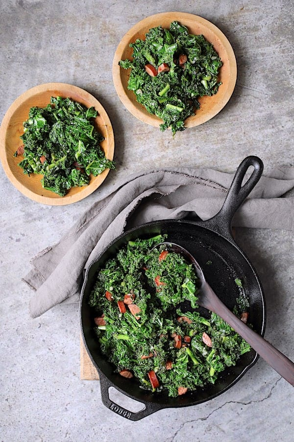 Spicy Sautéed Kale with Andouille Sausage - Overhead shot of dish being served from cast iron skillet onto wooden plates