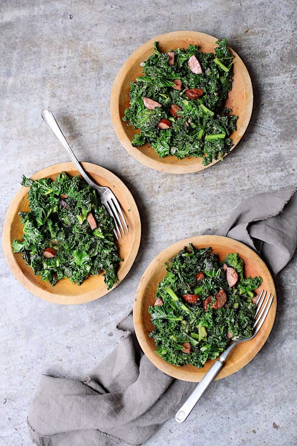 Spicy Sautéed Kale with Andouille Sausage - Overhead shot of three small wooden plates filled with this dish on gray background