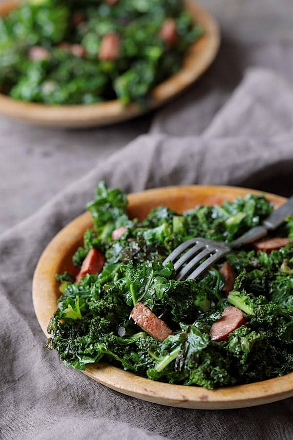 Spicy Sautéed Kale with Andouille Sausage - Straight-on close-up shot of dish on wooden plate with fork stuck into sausage and kale on gray background